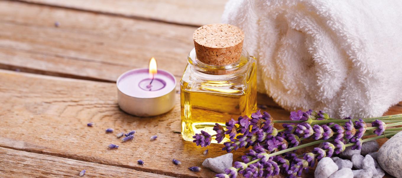 Teelicht, Glasflasche mit Flüssigkeit und zusammengerolltes Handndtuch, davor liegt Lavendel